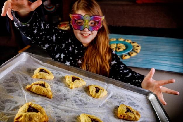 Una ragazza ebrea con i capelli lunghi si diverte e balla in maschera con i biscotti.