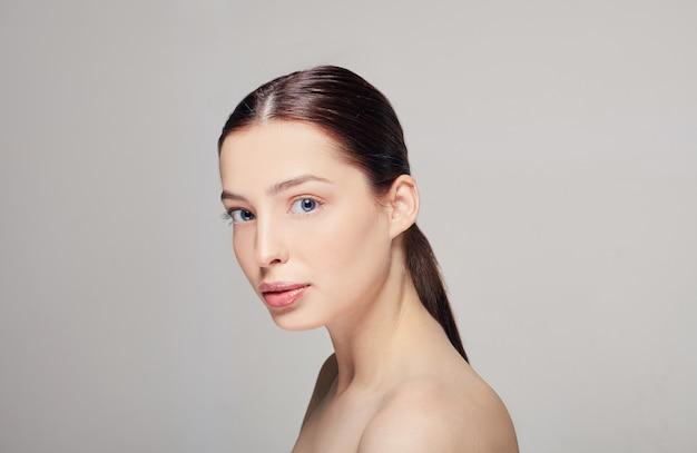 Una ragazza elegante e sofisticata con labbra carnose, capelli castano scuro e una pelle delicata e radiosa e delicata sul grigio. donna ben curata. spa.