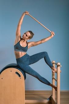 Una ragazza fa esercizi di pilates con un riformatore del letto, una macchina utensile a botte