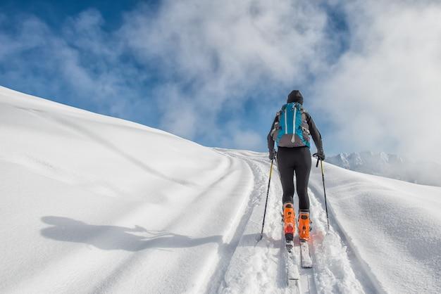 Una ragazza fa sci alpinismo