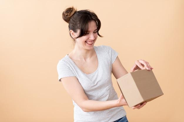 Una ragazza felice apre una scatola di artigianato e ci guarda curiosamente. una piacevole sorpresa per le vacanze