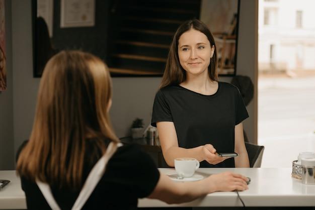 Una ragazza felice con i capelli lunghi che sorride e paga per il suo caffè con uno smartphone con la tecnologia pay pass senza contatto in un caffè. un barista femmina bruna tiene un terminale per pagare ad un cliente.