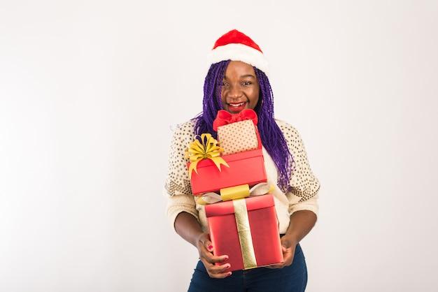 Una ragazza felice dalla pelle scura tiene in mano molti regali rossi.