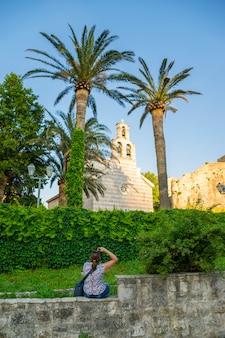 Una ragazza fotografa scatta foto di una chiesa tra le palme verdi.