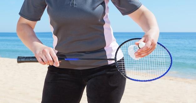 Una ragazza gioca a badminton sulla spiaggia. avvicinamento.