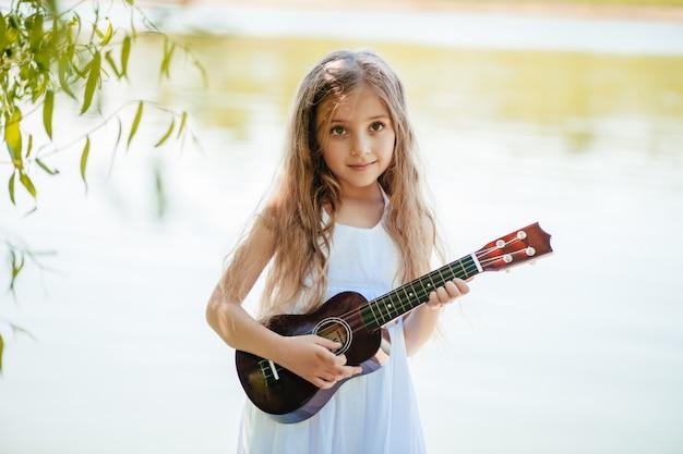 Una ragazza gioca ukulele in vacanza al mare., le donne sta trovandosi sulla spiaggia tropicale con cappello di paglia.