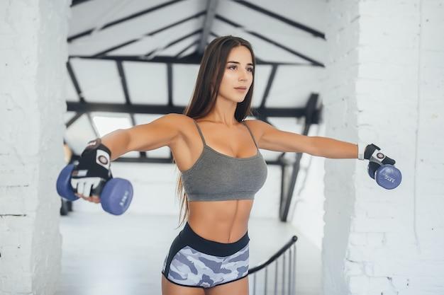 Una ragazza giovane, bella sport facendo esercizi sulle sue spalle in palestra