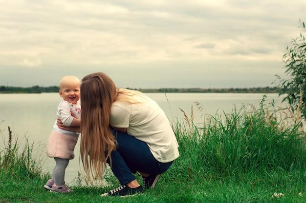 Una ragazza impara a camminare con sua madre in natura. mamma e figlia, apprendimento e sviluppo. i primi passi del bambino. momenti felici di vita.
