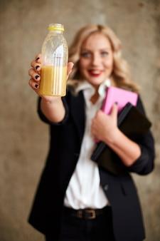 Una ragazza in abito beve il succo da una bottiglia e sorride. consegna del cibo