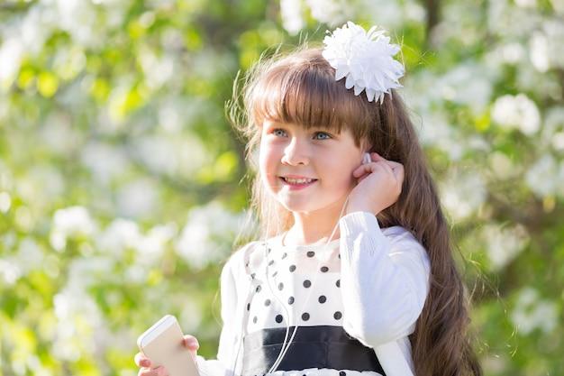 Una ragazza in abito bianco ascolta la musica attraverso piccole cuffie audio.