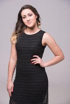 Una ragazza in abito nero è magnificamente in piedi.