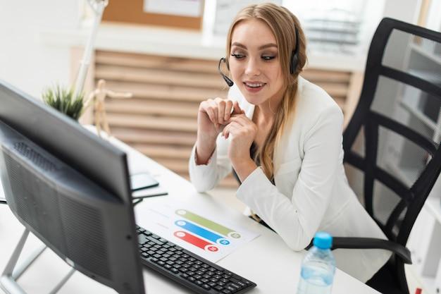 Una ragazza in cuffia con un microfono si siede a un tavolo in ufficio e guarda il monitor.