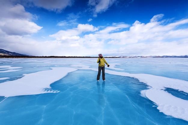 Una ragazza in giacca gialla e pattini da ghiaccio si trova sul lago blu del lago baikal e guarda il cielo