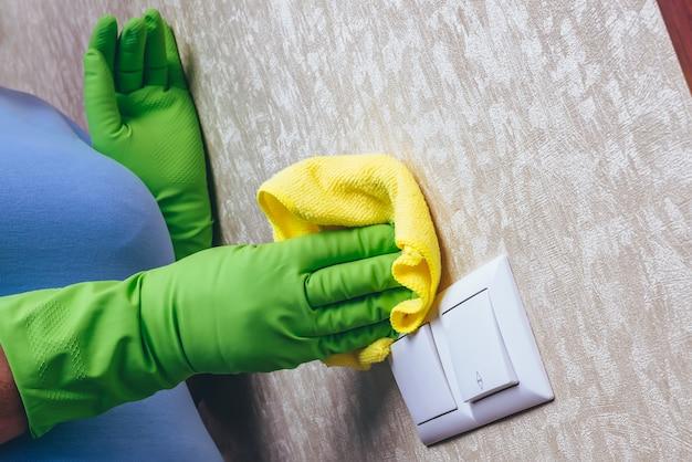 Una ragazza in guanti verdi pulisce l'interruttore elettrico con un panno giallo