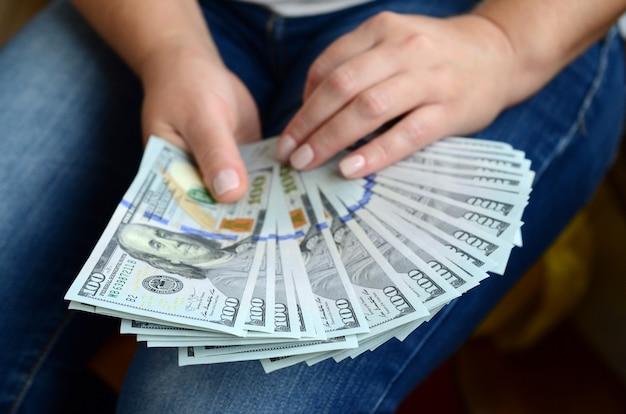 Una ragazza in possesso di un fan di banconote da un dollaro