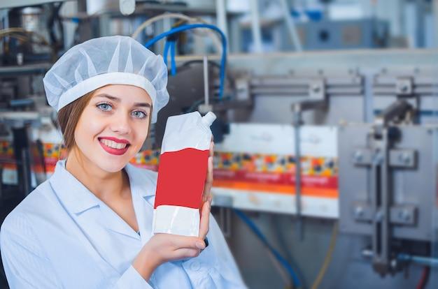 Una ragazza in tuta bianca e un copricapo sulla linea di produzione alimentare tiene in mano l'imballaggio dei prodotti.