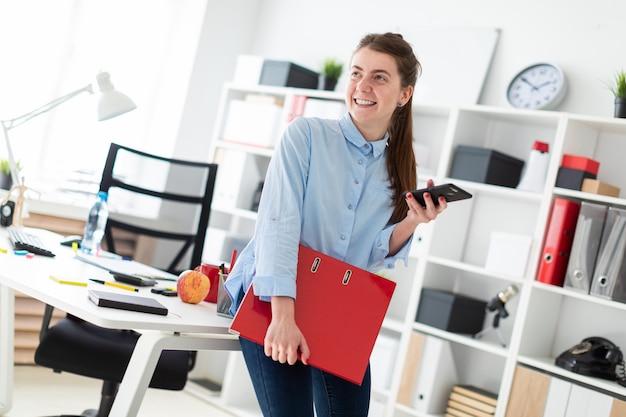Una ragazza in ufficio è in piedi, appoggiata a un tavolo, e tiene in mano un telefono e una cartella con i documenti.