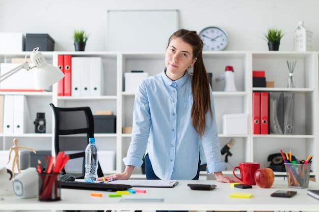 Una ragazza in ufficio è in piedi vicino al tavolo e ci mette le mani sopra.