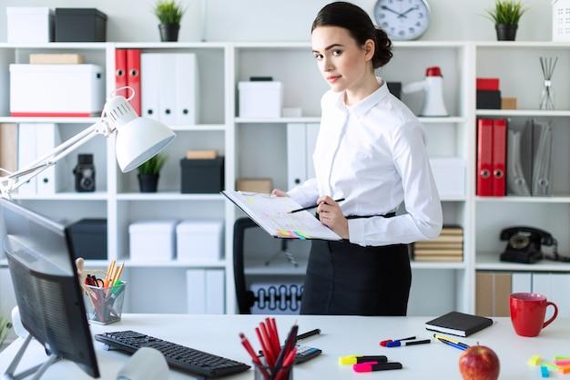 Una ragazza in ufficio è in piedi vicino al tavolo e tiene tra le mani un foglio per appunti e una matita.