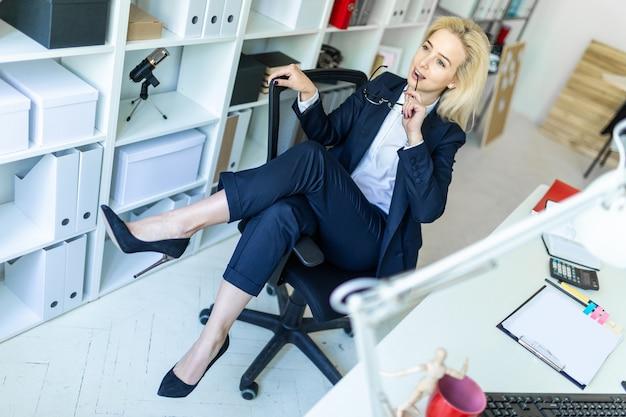 Una ragazza in ufficio si siede su una sedia e getta le gambe sul bracciolo.