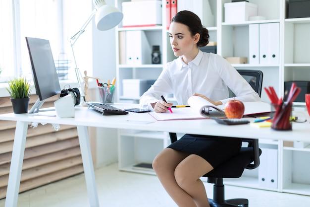 Una ragazza in ufficio tiene in mano un pennarello rosa e lavora con un computer e documenti.