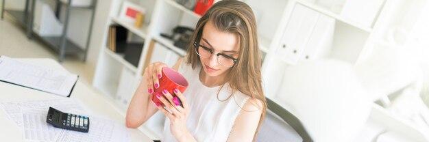 Una ragazza in ufficio tiene un pennarello rosa, una tazza rossa e lavora con i documenti.