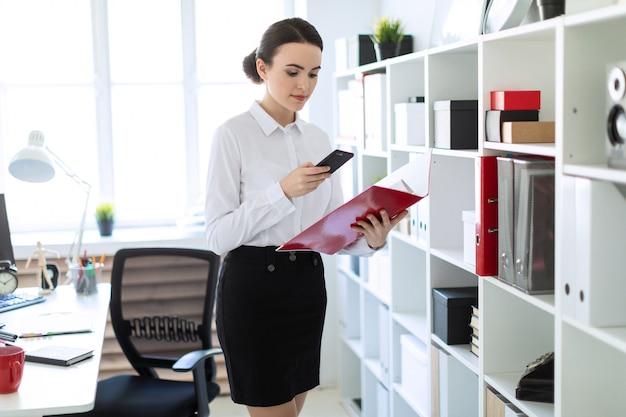 Una ragazza in ufficio vicino allo scaffale, con in mano una cartella con documenti e guardando nel telefono.