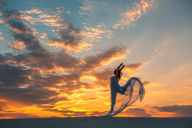 Una ragazza in un abito bianco vola balla e pone nel deserto di sabbia al tramonto