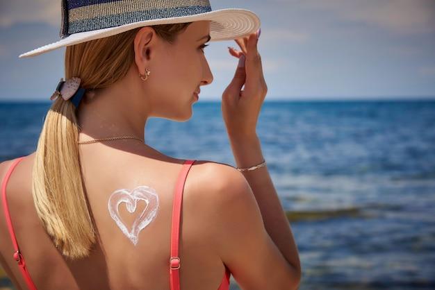 Una ragazza in un cappello con crema solare sotto forma di un cuore sulla schiena sulla spiaggia.
