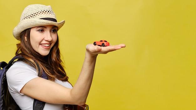 Una ragazza in un cappello tiene un'automobile del giocattolo sulla sua mano come concetto autostop. copia spazio.