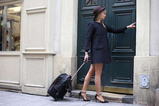 Una ragazza in un cappotto corto nero con cappello e valigia suona alla porta