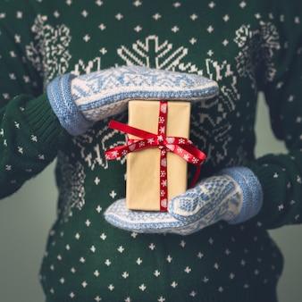 Una ragazza in un maglione di capodanno tiene un regalo. regali per uomini. buon natale. regalo per una ragazza maglione con ornamento di natale. abito in maglia