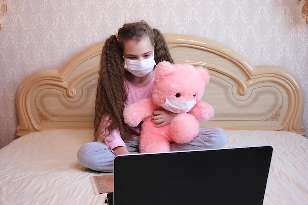 Una ragazza in una maschera con un orsacchiotto rosa in una maschera guarda un computer portatile