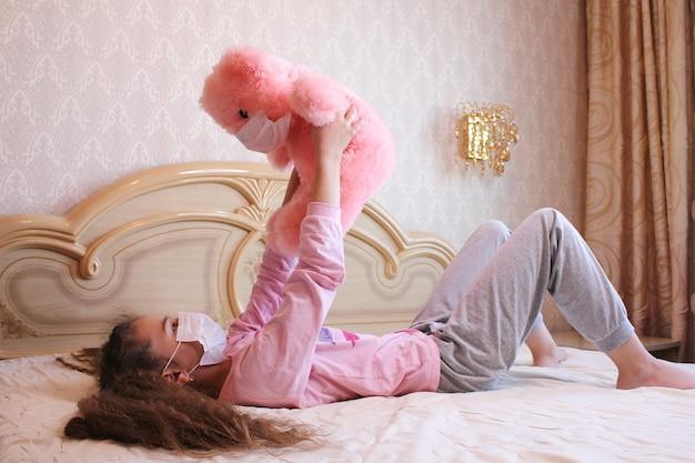 Una ragazza in una maschera gioca con un orsacchiotto rosa in una maschera.