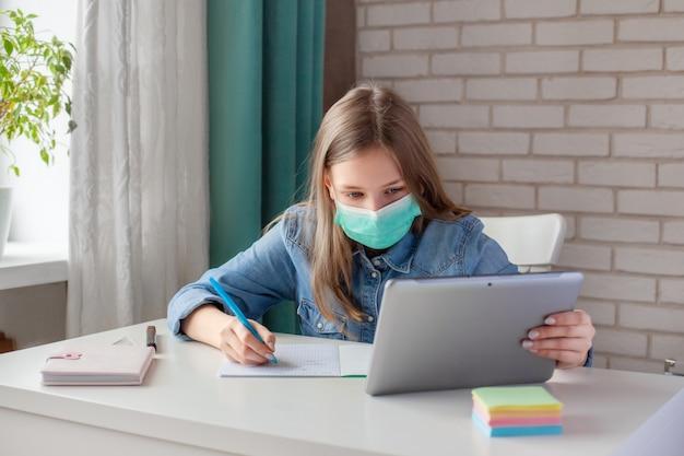 Una ragazza in una maschera medica sta studiando a casa con un laptop tavoletta digitale e sta facendo i compiti. formazione online a distanza