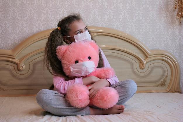 Una ragazza in una maschera per il viso abbraccia un orsacchiotto rosa in una maschera per il viso.