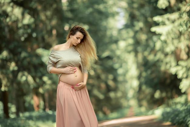 Una ragazza incinta è seduta nel parco e le accarezza la pancia.