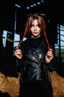 Una ragazza magra dai capelli rossi in una giacca di pelle nera tiene i capelli tra le mani