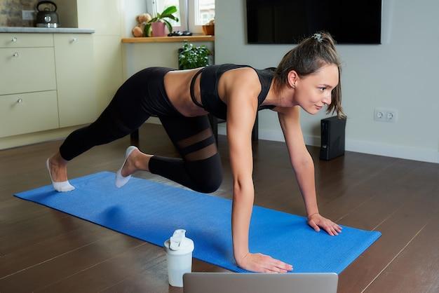 Una ragazza magra in un vestito attillato nero sta facendo esercizio per gli addominali e sta guardando un video di formazione online su un laptop. un allenatore che conduce una lezione di fitness a distanza sul tappetino yoga blu a casa.