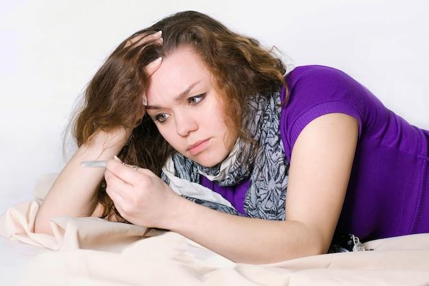 Una ragazza malata durante la pandemia di covid-19 guarda il termometro