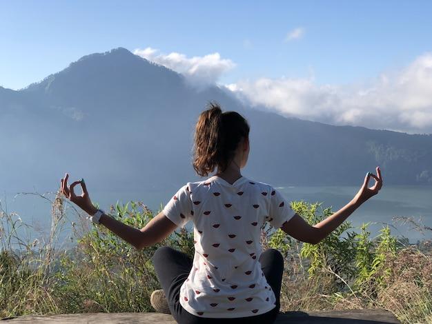 Una ragazza medita sulla montagna