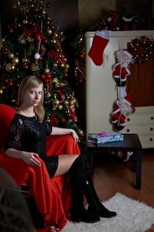 Una ragazza modello con i capelli biondi che sta esaminando la cornice. sfere dorate e rosse di natale su un albero di natale. tema di capodanno