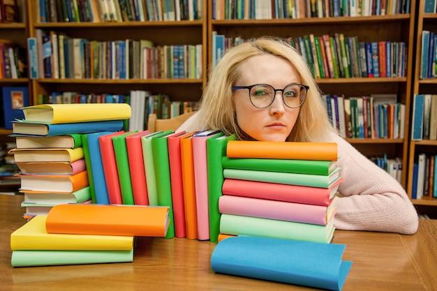 Una ragazza nella biblioteca sembra misteriosamente attraverso gli occhiali