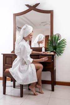 Una ragazza pone mentre era seduto a un tavolo da toeletta marrone in un accappatoio bianco e asciugamano