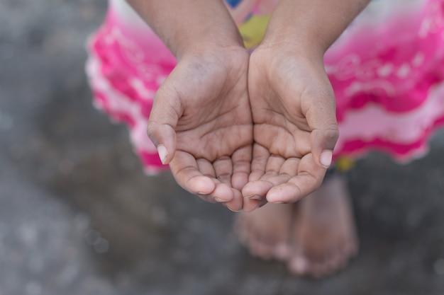 Una ragazza povera che solleva le mani elemosina un po 'di cibo o un po' di denaro in un concetto di vita povera