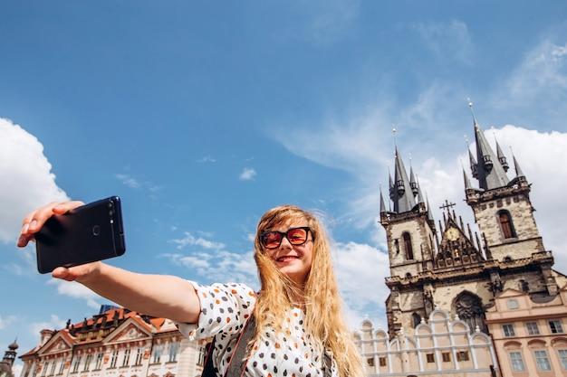 Una ragazza prende un selfie sul muro della chiesa di tyn. foto al telefono a praga. bella giovane donna che viaggia a praga. il turista felice della donna prende un selfie.