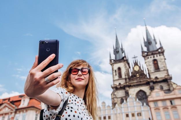 Una ragazza prende un selfie sullo sfondo della chiesa di tyn. foto al telefono a praga. bella giovane donna che viaggia a praga. il turista felice della donna prende un selfie.