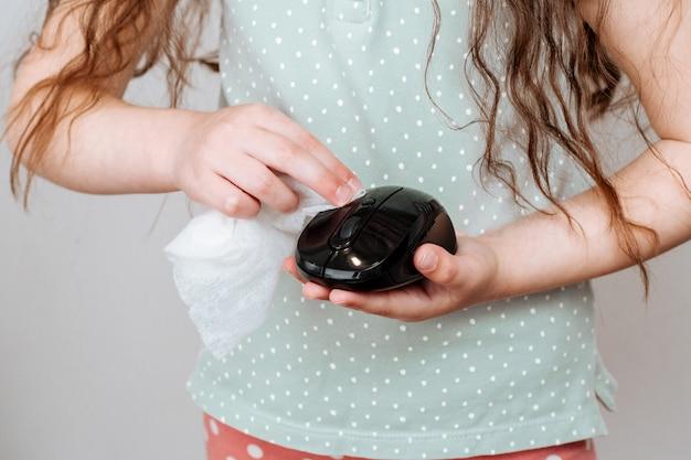 Una ragazza pulisce il mouse di un computer con un panno disinfettante.