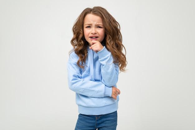 Una ragazza seria in una felpa con cappuccio blu casual sta con un'espressione onesta mentre tiene un dito alla bocca su un muro bianco con uno spazio vuoto