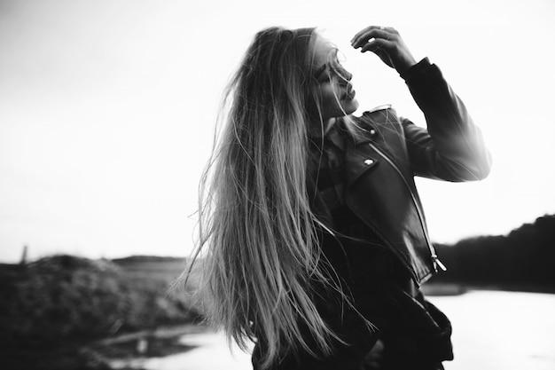 Una ragazza si pone sulla riva di un lago